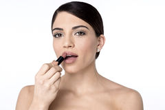 This colour perfectly match. Pretty woman applying lipstick on her lips Royalty Free Stock Image