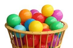 Colour plastikowe piłki w koszu nad białym tłem Obrazy Stock