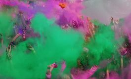 Color Run dust and hands in the air. People are covered in colored dust at the color run in Bucharest, Romania. Group of people with hands in the air at the royalty free stock photo