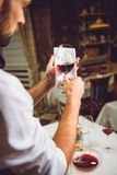 Colour saturation of red wine. Sommelier is holding wineglass with scarlet nectar against serviette Stock Photos