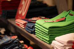 Colour shirts at shelf in shop Royalty Free Stock Photography