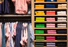 Colour shirts at shelf in shop Royalty Free Stock Photos