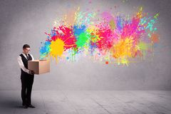 Colour splatter from box. A young smiling business male holding a paperboard box with illustration of colourful spray paint splash on urban wall background Royalty Free Stock Images