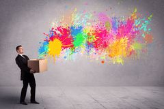 Colour splatter from box. A young smiling business male holding a paperboard box with illustration of colourful spray paint splash on urban wall background Royalty Free Stock Photo