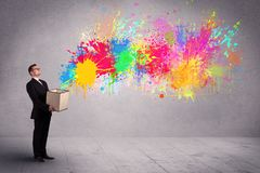 Colour splatter from box. A young smiling business male holding a paperboard box with illustration of colourful spray paint splash on urban wall background Stock Image