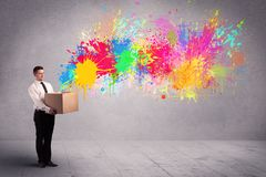 Colour splatter from box. A young smiling business male holding a paperboard box with illustration of colourful spray paint splash on urban wall background Royalty Free Stock Photography