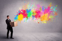 Colour splatter from box. A young smiling business male holding a paperboard box with illustration of colourful spray paint splash on urban wall background Stock Photo