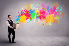 Colour splatter from box. A young smiling business male holding a paperboard box with illustration of colourful spray paint splash on urban wall background Stock Images