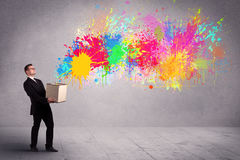 Colour splatter from box. A young smiling business male holding a paperboard box with illustration of colourful spray paint splash on urban wall background Royalty Free Stock Photos