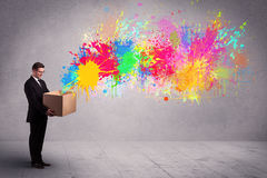 Colour splatter from box. A young smiling business male holding a paperboard box with illustration of colourful spray paint splash on urban wall background Stock Photos