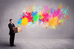 Colour splatter from box. A young smiling  male holding a paperboard box with illustration of colourful spray paint splash on urban wall background concept Royalty Free Stock Images