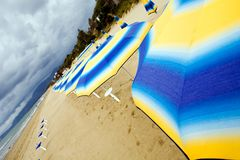 Colour sunshades on a empty beach. In southern Italy Royalty Free Stock Photography