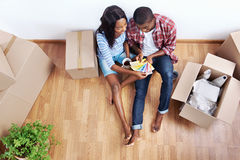 Colour swatch home. Overhead view of young black african couple with moving boxes in new apartment choosing colour of paint for walls Royalty Free Stock Image