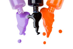 Colour varnish. The colour nail polish which is pouring out from bottles on a white background Stock Photography
