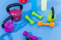 Colour weights, dumbbells,Kettlebells and isotonic drinks at gym. Indoor photo Stock Photography