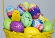 Coloured绘了鸡蛋,并且玩具小鸡在复活节的一个篮子显示 免版税库存照片