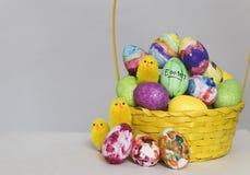 Coloured绘了鸡蛋,并且玩具小鸡在复活节的一个篮子显示 图库摄影