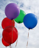 Coloured balloons floating. In a cloudy sky Royalty Free Stock Photo