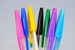Coloured ballpoint pens. Coloured ballpoint pens against a grey background stock image