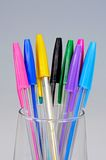 Coloured ballpoint pens. Coloured ballpoint pens in a glass against a grey background stock image