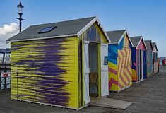 Coloured beach huts at the end of the pier. stock photography