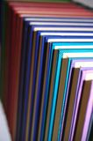 Coloured books in neat row Royalty Free Stock Images