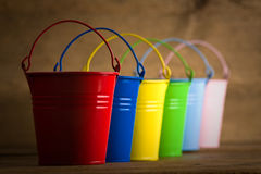 Coloured buckets on the floor. Six coloured buckets in one diagonal line on timber floor royalty free stock image