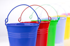 Coloured buckets in line Stock Images
