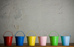 Coloured buckets in line on the floor royalty free stock image