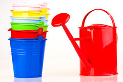 Coloured buckets and watering can. Five coloured buckets in one diagonal line with red watering can Stock Photos