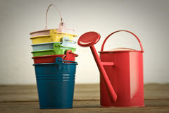 Coloured buckets and watering can on the floor. Six coloured buckets in column with red watering can on timber floor Stock Image