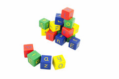 Coloured building blocks with letters on a white background. Child's building blocks in primary colours on a white background. The word at the front spells 'play Stock Photo