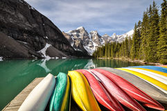 Coloured canoes in Canada. A line of multi-coloured canoes at Moraine Lake shoreline. Alberta, Canada royalty free stock images