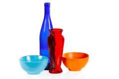 Coloured ceramic cups, glass bottle and vase Stock Photo