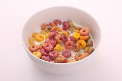 Coloured cereal with milk , breakfast meal. Delicious cereals coloured cereals with milk in white bowl Breakfast meal white dish White background royalty free stock images