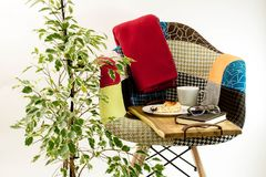Coloured chair with blanket and wood tray near plant. Coloured patchwork chair with blanket and wood tray with old notebook, cup, glasses and cake on white plate stock images