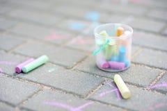 Coloured chalks on a sidewalk. Coloured chalks in a bucket on a sidewalk royalty free stock photography