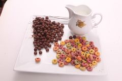 Coloured and chocolate cereal - breakfast meal. Delicious cereals coloured andcereals chocolate cereals Breakfast meal white dish White background royalty free stock photo