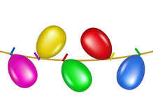 Coloured clothespins on rope holding balloons Royalty Free Stock Images