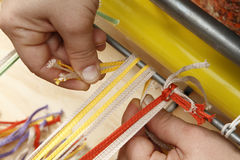 Coloured cords. Hands weaving coloured cords on loom stock images