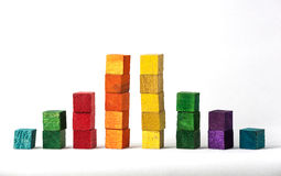 Coloured Cubes on White Background. Blue, green, red, orange, yellow and purple stacked wooden cubes isolated on white background Royalty Free Stock Image