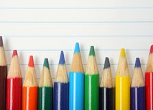 Coloured Drawing Pencils. On a background of lined paper from a school book with copy space royalty free stock images