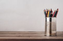 Coloured Drawing Pencils in Metal Tin on Wood Plank Desk. A variety of coloured pencils in an old metal tin on a wood plank desk with copy space to left and stock images