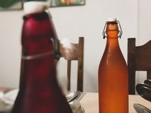 Coloured drink bottles with a rustic edge on a solid wooden dining table at a home indoors. royalty free stock photo