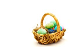 Coloured Easter eggs in the basket. Coloured Eaaster eggs in the basket, a bit covered with straw on white background Stock Image