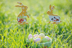 Coloured Easter eggs in a basket with rabbit decorations Stock Photography