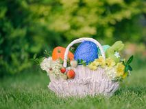 Coloured eggs, bunny, flowers and berries in Easter gift set basket Royalty Free Stock Photography