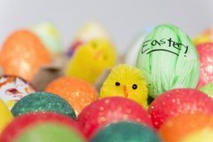 Coloured easter eggs and baby toy chick. Coloured eggs and a toy chick are shown ahead of Easter stock image