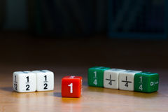 Coloured fraction dices on wood table royalty free stock photo