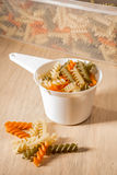 Coloured fussily in measuring cup infront of container filled wi Royalty Free Stock Photography